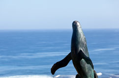 Statue of whale breaching with sea Stock Photo