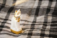 Statue of white Egypt cat on checked blanket surface. Traditional egyptian gift element. Statue of white Egypt cat on checked blanket surface. Traditional Royalty Free Stock Image