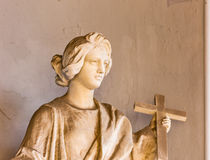 Statue of woman with Christian cross Stock Images