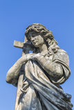 Statue of a woman with a cross Stock Photography