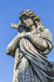 Statue of a woman with a cross Royalty Free Stock Photos