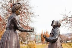 Statue of a woman handing a girl an apple in the Boise Rose Garden. On a cloudy winter day Stock Images