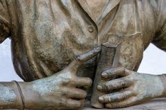 Statue of a woman holding a book in her hands royalty free stock photos