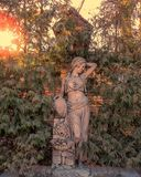 Statue of a woman with a jug in the evening garden royalty free stock images
