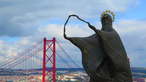 Statue of woman looking at Cristo Rei Stock Photography