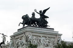 Statue of a woman riding a horse carriage in Vienna Austria. Against a white sky. The woman is carrying a laurel wreath. The Roman style statue also contains Royalty Free Stock Image