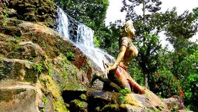 Statue of woman on waterfall in the jungle forest. Stock Images