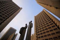 Statuen unter Hochhäusern stockfotos