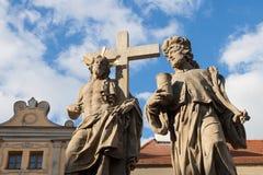 Statuen von Christus und von Mann und Kreuz gegen blauen Himmel Stockbilder