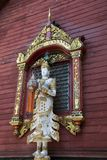 Statuenholdinglaterne vor geschnitztem Fensterrahmen und rote Wand bei Wat Ming Muang lizenzfreie stockfotos