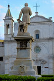 Statuenmonument vor einer Kirche Stockbild