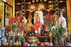 Statues bouddhistes d'or avec les fleurs et les fruits rouges Photographie stock libre de droits