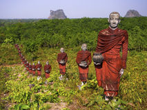 Statues of Buddhist Monks in the Forest, Mawlamyine, Myanmar. Hundreds of statues of Buddhist monks collecting alms surround the massive Win Sein Taw Ya Buddha stock image