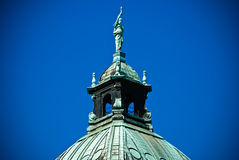 Statues on a building. Domes of a building of court of a city of Leipzig against the blue summer sky Stock Photo
