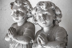 Statues of children in prayer. Covered with cobwebs Stock Photography