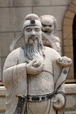 Statues of Chinese deity and lion sculpture. Royalty Free Stock Image