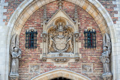 Statues and coat of arms over archway. Royalty Free Stock Images