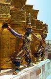 Statues colorées de démon entourant la base d'un chedi photo stock