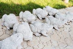 Statues de chaux des grenouilles Passage couvert en pierre Grenouilles sur l'allée dans le beau jardin avec des fleurs et des arb Images libres de droits