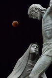 Statues and eclipse of the Moon Stock Photo