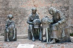Statues of embroiderers with craft wires in the city of Offida i. Monument of embroiderers with handcrafted threads in the medieval town of Offida in the royalty free stock image