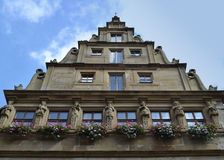 Statues and Flowers and a Fascinating Roof. A fascinating building with statues line up on the front in Rothenburg ob der Tauber. In the town district of Ansbach royalty free stock photography