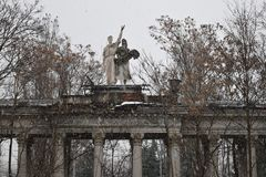 Statues in the garden during a snowfall stock images