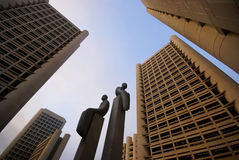 Statues among high-rises. Two bronze statues among modern concrete high-rises at sunset stock photos