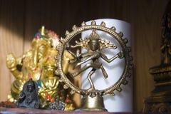 Statues of Hindu gods. Shiva and Ganesha and white candle stock images