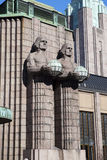 Statues holding the spherical lamps at the Helsinki Central railway station on march 17, 2013 in Helsinki, Finland. Royalty Free Stock Photography