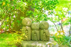 Statues of Jizo. Three statues of Jizo in a foliage blur background. Hase-dera in Kamakura, Japan. Hasedera is one of the largest Buddhist temples in the city stock photos