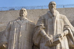 Statues of John Calvin and William Farel. On the reformation wall in Parc Des Bastions, Geneva, Switzerland Royalty Free Stock Image