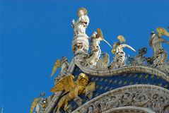 Statues of lion, angels and Jesus Christ decorating upper facade of the Saint Mark`s Basilica in Venice, Italy. stock photo