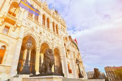 Statues of lion sculpture at the entrance to parliament famous building in Budapest, Hungary. Hungarian flag on blue clouds sky on. Sunset. Popular travel royalty free stock image