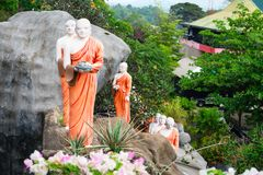Statues of monks in Golden cave temple in Dambulla, Sri Lanka. Statues of monks on a rock with flowers in Golden cave temple in Dambulla, Sri Lanka Royalty Free Stock Photo