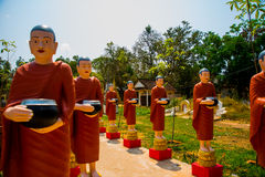 Statues of monks at the temple. Siemreap,Cambodia. Sculptures of priests in red clothes, in the hands of the bowl.Siemreap,Cambodia royalty free stock photo