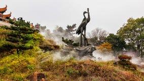 Statues par la tour jaune de grue à Wuhan, Chine photos stock