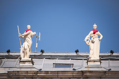 Statues on the roof of the city hall of Bayonne with a red scarf during the Summer festival Royalty Free Stock Photo