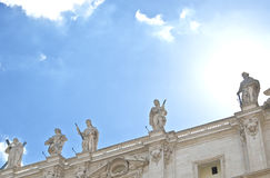 Statues on the roof of St. Petes Basilica. Above the head of one of the sculptures sun shines and reminds halo. Stock Image
