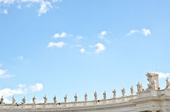 Statues on the roof of St. Peter's Basilica against the blue sky. Stock Photo