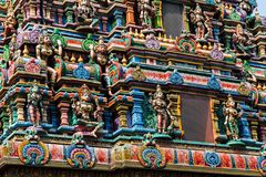 Statues on a spire at a Buddhist temple. Colorful statures decorate the spire of a Buddhist temple in Bangkok Thailand. The intricate design is beautiful Royalty Free Stock Photo