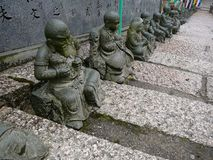 Statues on the Stairs of a Temple in Japan. Small statues on the stairs of a buddhist temple in Miyajima, Japan. I believe they depict deceased monks, the names stock photos