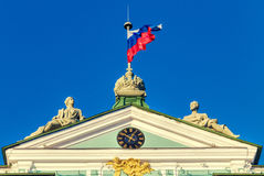 The statues and the state flag on the top of the Hermitage building. Saint Petersburg, Russia. The statues and the state flag on the top of the Hermitage royalty free stock photo