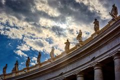 Statues on top of the Tuscan colonnades. VATICAN CITY, VATICAN - MAY 17, 2017: Some of the statues on top of the Tuscan colonnades in Saint Peter's square in Stock Photo