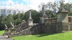 Statue and staircase in the park. Statues and trees- varieties of different statues in a park with different types of trees and a stadium in the background stock video