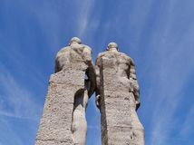 Statues of two athletes from the back. At Berlin Olympiastadion, shot from below against blue sky Stock Images