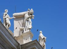 Statues on Vatican roof, Rome, Italy. A shot of a corner of the the Vatican roof, against a bright blue sky, showing white marble statues Stock Photos