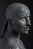 Statuesque woman in wet clay. Spa treatment. Royalty Free Stock Photography