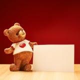 Statuetta ceramica dell'orso accanto ad una cartolina d'auguri Fotografia Stock