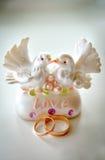 Statuetta delle colombe e delle fedi nuziali Fotografie Stock Libere da Diritti